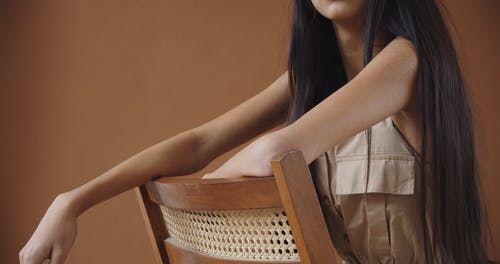 A Young Woman Leaning on a Chair