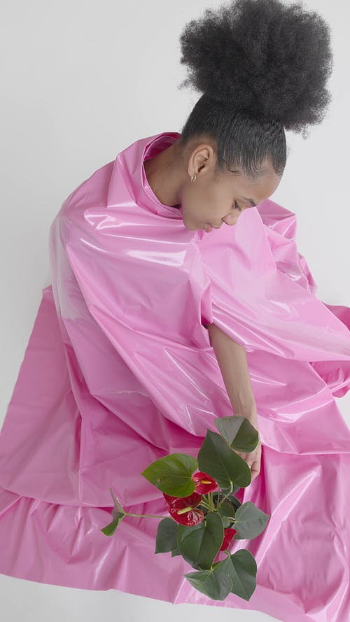 Woman Covered with Pink Plastic Touching a Plant