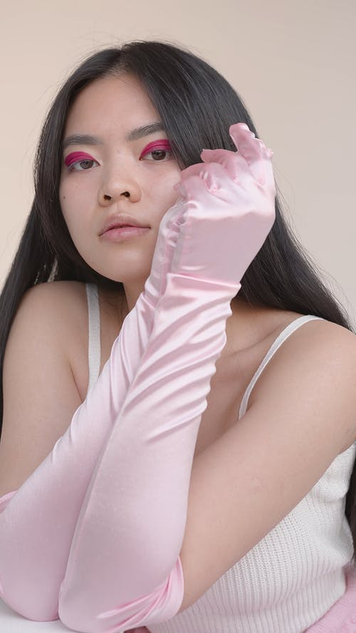 A Woman Posing in Pink Evening Gloves