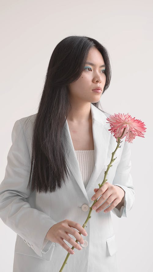 A Woman in a Suit Jacket Posing with a Pink Flower