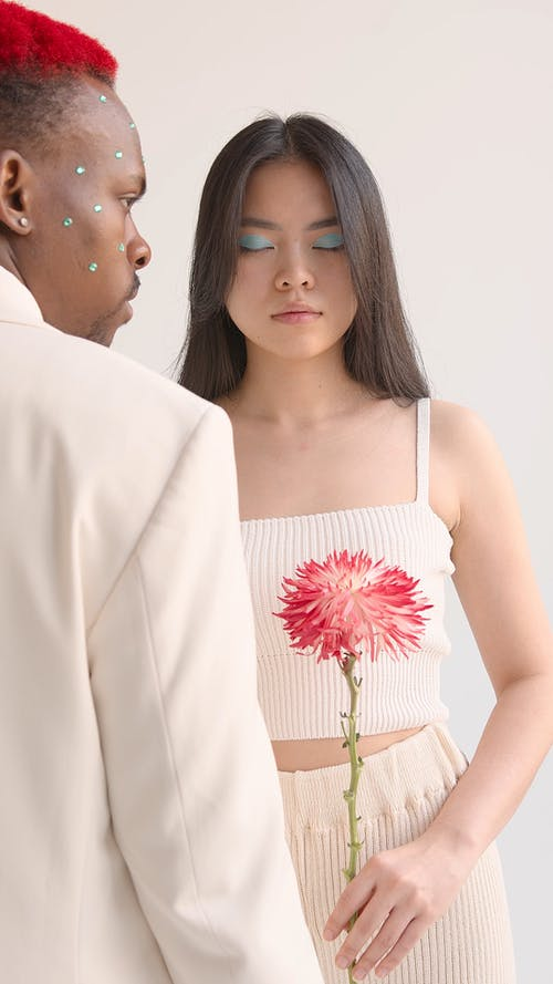 Couple in Beige Clothing Holding a Flower