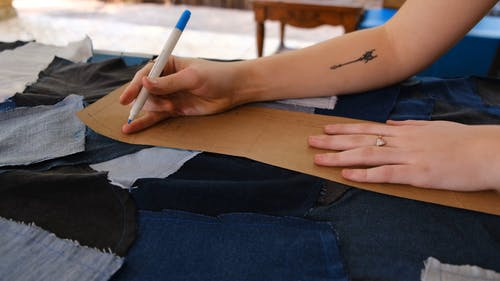 A Person Marking the Denim Fabric