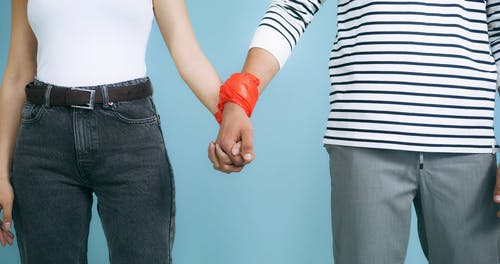 A Man and a Woman with Plastic Wrapped around their Wrist Holding Hands
