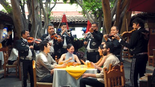 A Band Playing Mariachi Music For Guests In A Restaurant