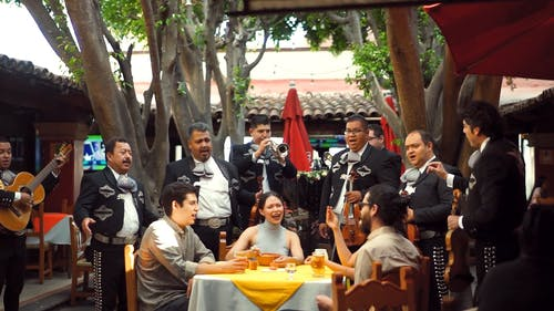 A Mexican Band Entertaining Diners In An Open Restaurant