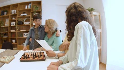 Elderly Man Teaching Kids the Rules of Chess