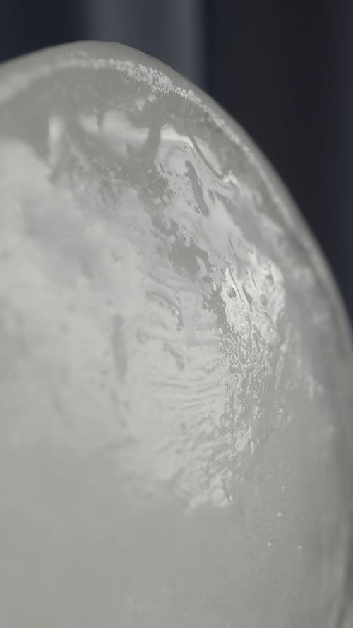 Drops of Clear Liquid on a White Surface