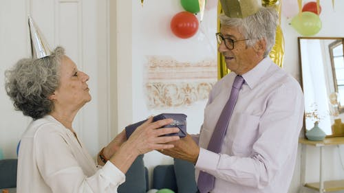 Elderly Couple Wearing Party Hats Hugging Each Other