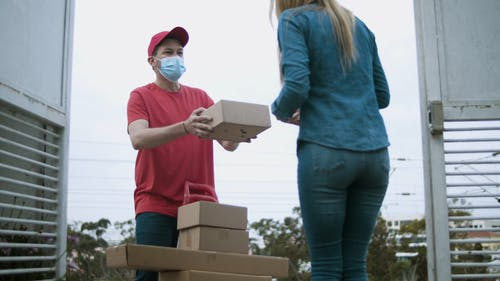 A Deliveryman Giving to the Woman the Online Purchase