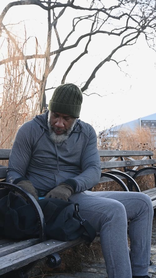 A Man Sitting on a Bench while Fixing His Bag