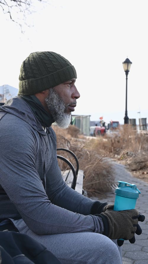 Bearded Man Resting on a Bench Drinking Water