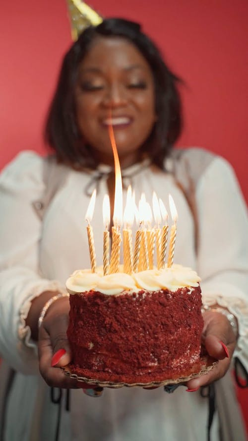 A Woman Blowing Candle on a Cake