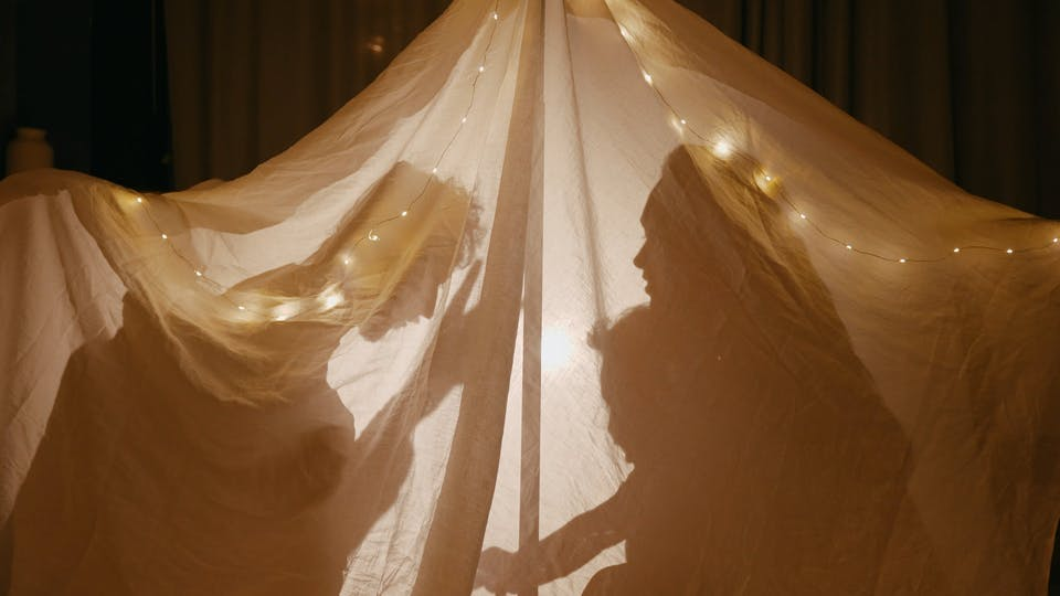 Silhouette Of A Family Playing Together Behind A Blanket