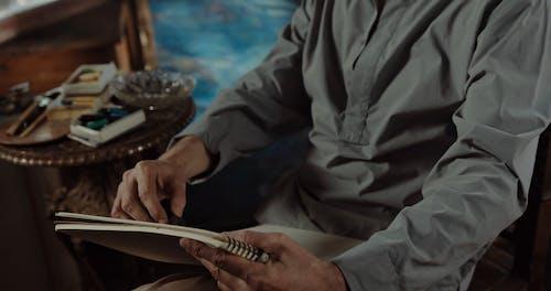 Elderly Man Sketching Using Charcoal