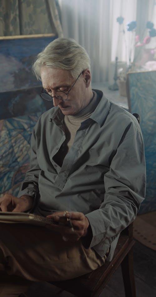 Elderly Man Sketching while Smoking