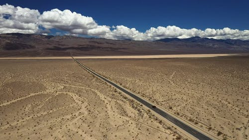 A Car Driving on a Road in Death Valley