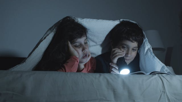 Children Reading A Book Together On A Bed