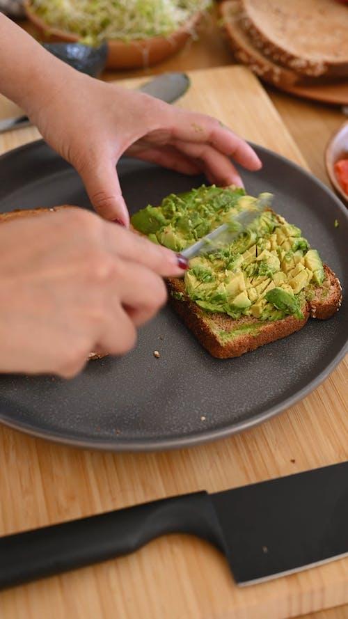 Person Mashing Avocado on Bread