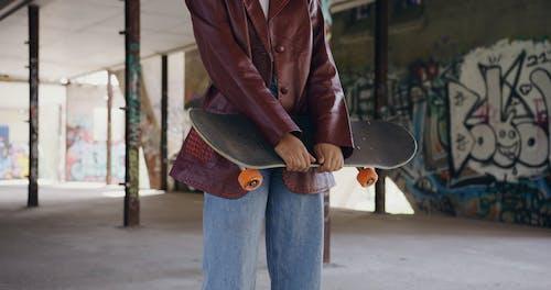 Female Holding a Skateboard in a Skate Park