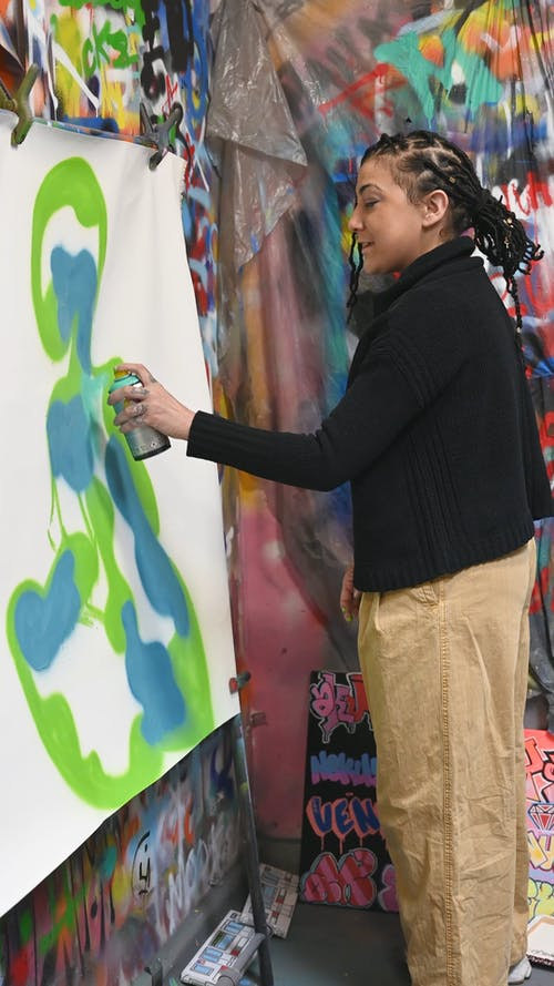 Woman Spray Painting on a Cloth Canvas