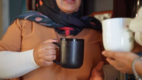 A Waman Holding a Cup of Coffee