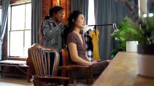 Woman Braiding Her Friend's Hair