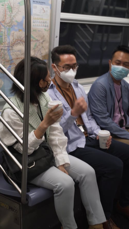People Wearing Face Masks while Riding a Train