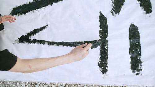 Person Writing Japanese Characters On White Textile