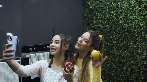 Girls Having a Selfie while Holding Vegetables