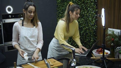Girls Using Laptop while Cooking