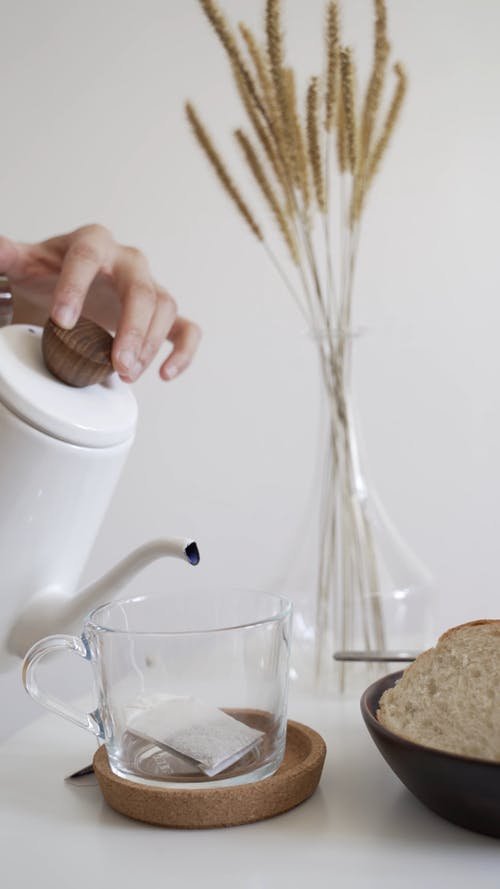 Person Pouring Hot Water to the Glass with Tea Bag