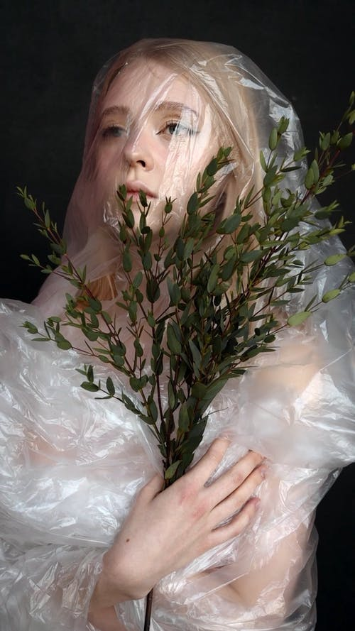 Female Model Covered in Plastic Holding Plants