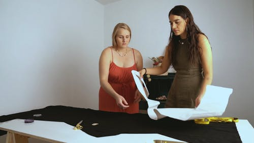 Women Laying Out a Stencil on Top of Fabric