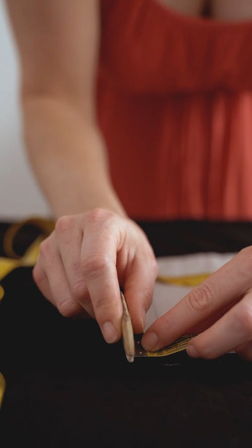 A Woman Using a Tailors Chalk on Fabric