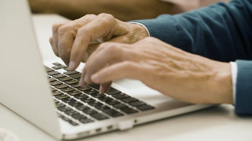 Close Up of an Elderly Person's Hands Typing on a Laptop