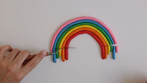 A Person Cutting the Ends of a Clay Rainbow