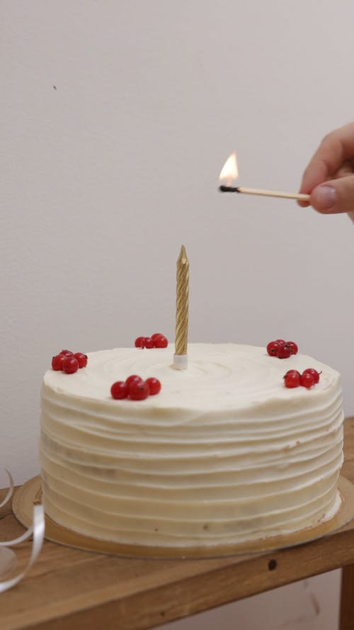 Person Lighting a Candle with a Matchstick