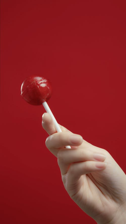 Close Up View of a Person Holding a Lollipop