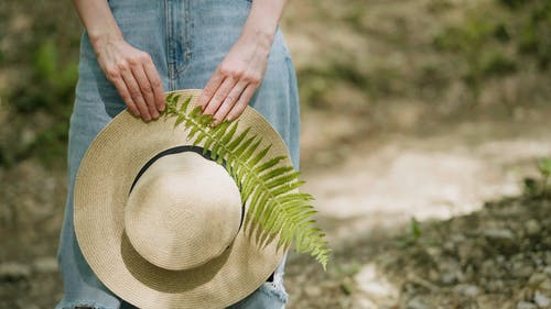 A Person Holding a Sun Hat and a Fern Leaf