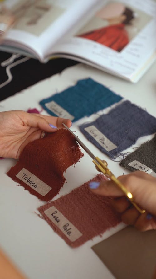 A Female Person Cutting a Swatch on a Table