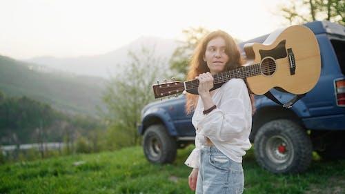 Woman Walking While Holding Guitar