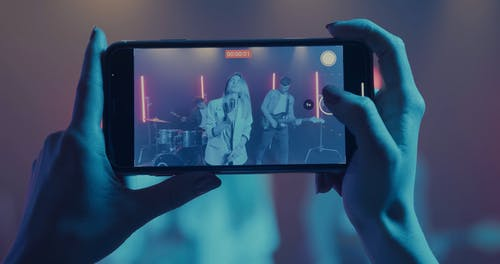 A Woman Video Recording the Perfomance of a Band with a Cellphone