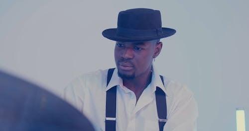 Man Wearing Hat Playing Drums