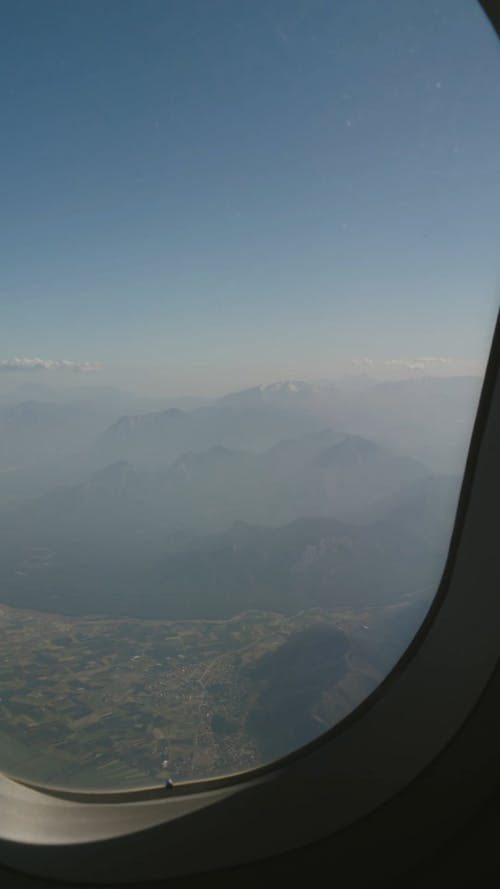 View Of Foggy Mountains From An Airplane Window