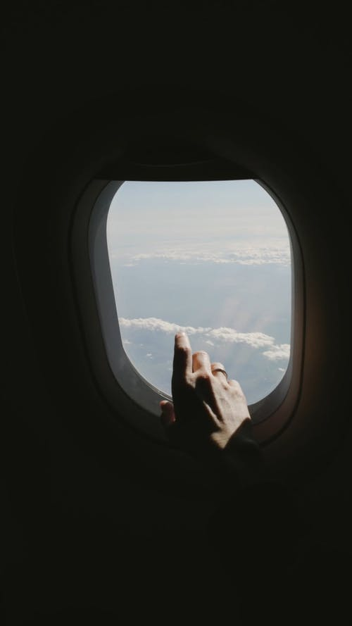 A Person Touching the Window in the Airplane