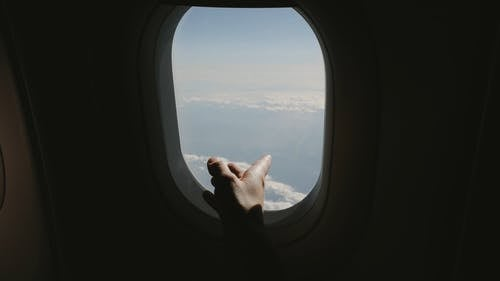 Close Up View of a Person Touching the Airplane Window