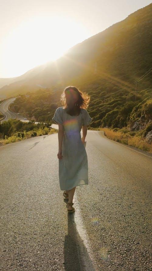 A Woman Walking on an Empty Road