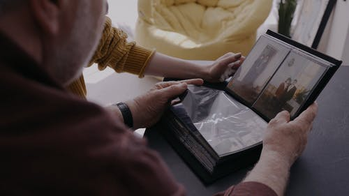 A Man and a Woman Looking at a Photo Album