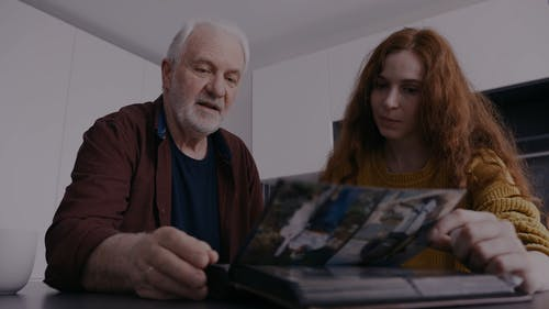 A Father And Daughter Looking At A Photo Album