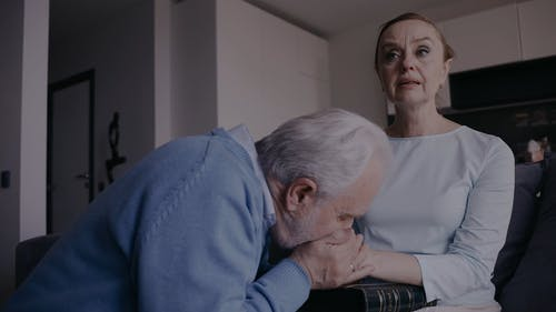 An Elderly Woman Crying While an Elderly Man Comforting Her